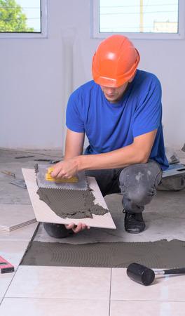industrial tiler builder worker installing floor tile