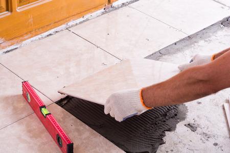 Tiler installing ceramic tiles on a floor