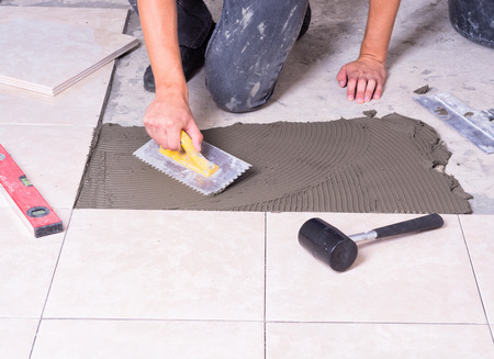 install: Tiler installing ceramic tiles on a floor