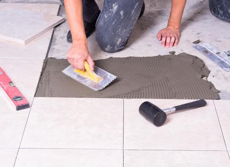 Tiler installing ceramic tiles on a floor Banco de Imagens - 43169079