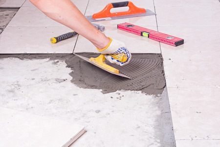 Tiler installing ceramic tiles on a floor Banco de Imagens - 43169085