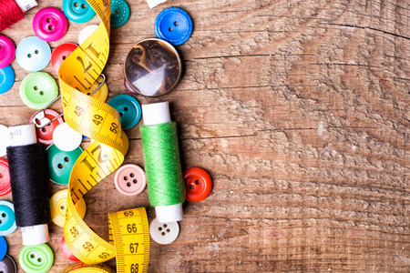 old spools: Spools of threads and buttons on old wooden table Stock Photo