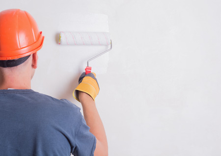 Painter On Stepladder Painting Wall With Brush Stock Photo
