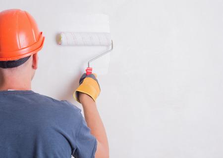 pintor: Pintor en la escalera pintura de pared con el cepillo Foto de archivo