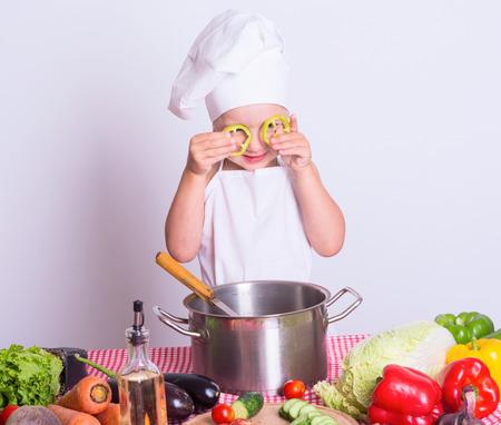 niños comiendo: Pequeño cocinero prepara una comida de verduras Foto de archivo