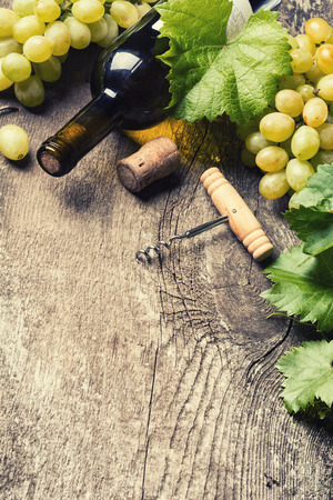 des vins: Bottle of white wine, grape and corks on old wooden background