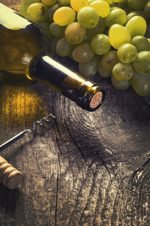 Bottle of white wine, grape and corks on old wooden background