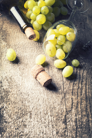 vins: Bottle of white wine, grape and corks on old wooden background