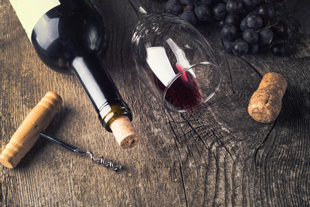 des vins: Bottle of dark wine , grape and corks on old wooden background