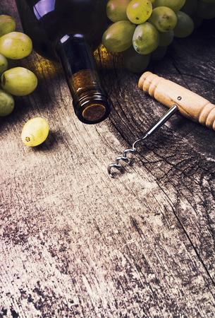 des vins: Bottle of white wine , grape and corks on old wooden background Stock Photo