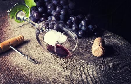 des vins: Bottle of dark wine, grape and corks on old wooden background