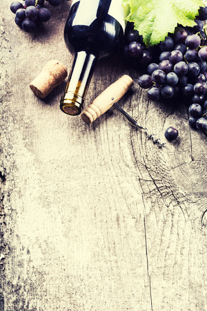 Bottle of dark wine, grape and corks on old wooden background