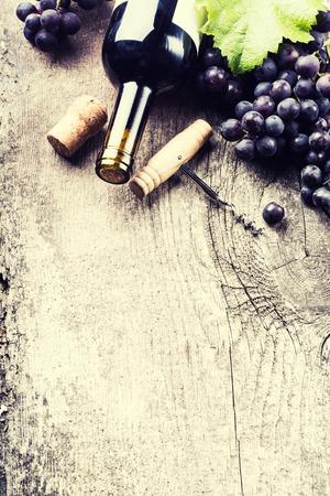 Fles donkere wijn, druif en kurken op oude houten achtergrond