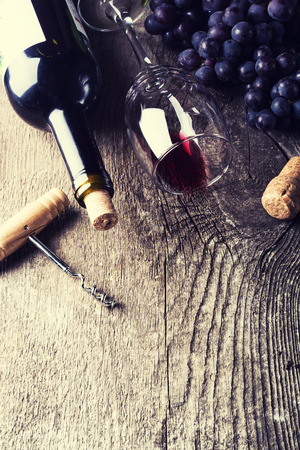 des vins: Bottle of dark wine, grape and corks on old wooden background