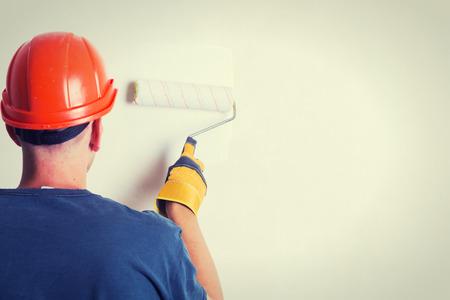 pintor de casas: Pintor en la escalera pintura de pared con el cepillo Foto de archivo