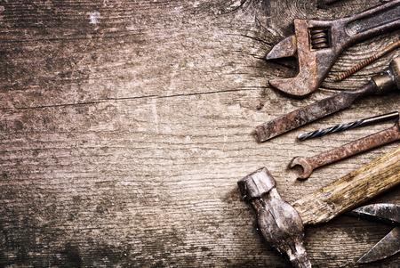 herramientas de trabajo: Juego sucio de herramientas de mano sobre un fondo de madera. foto de época Foto de archivo