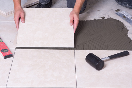 install: Tiler installing ceramic tiles on a floor . Stock Photo