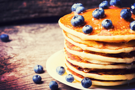 Pancakes with blueberries & honey on wood background .