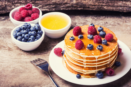Pancakes with blueberries, honey & raspberry on wood background Banco de Imagens