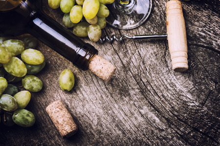 des vins: Bottle of white wine, glass, grape and corks on old wooden background