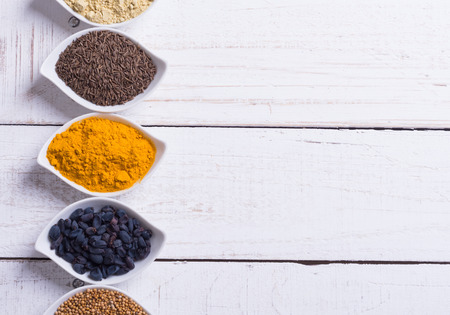 dry food: Spices and herbs in ceramic bowls on wooden background . Traditional Indian food .