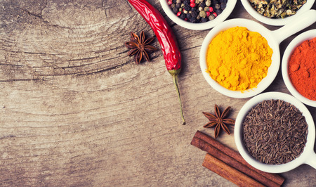 Spices and herbs in ceramic bowls on wooden background . Traditional Indian food .
