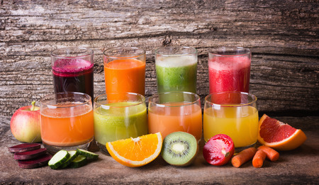 Succo di frutta e di verdure sano su sfondo di legno