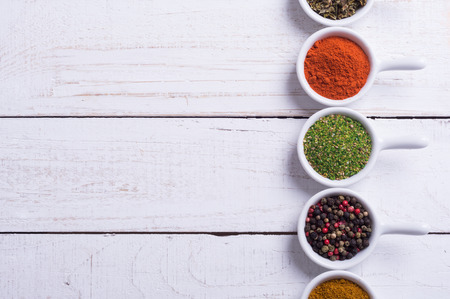 indian cooking: Spices and herbs in ceramic bowls on wooden background . Traditional Indian food .