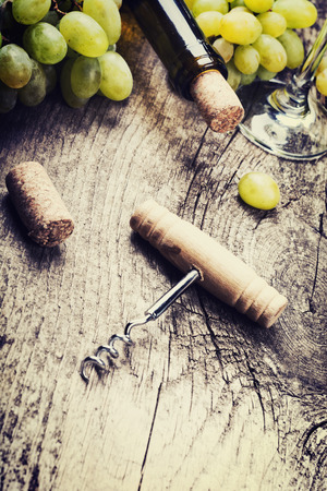 vins: Bottle of white wine, glass, grape and corks on old wooden background