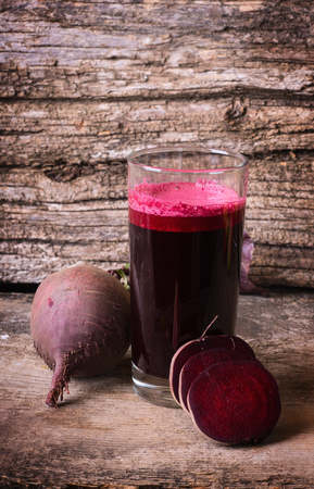 Glass of beet juice with beets on wooden table Stock Photo