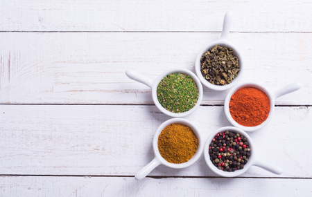 herbs: Spices and herbs in ceramic bowls on wooden background . Traditional Indian food .