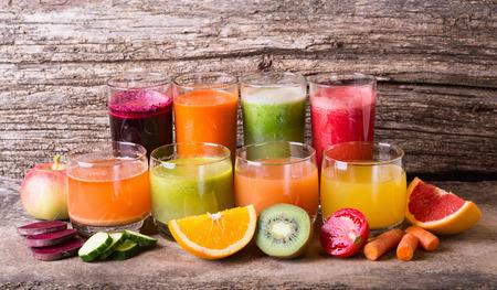 jugos: Jugo saludable de frutas y verduras en el fondo de madera
