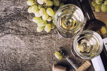 des vins: Bottle of white wine, glass, grape and corks on old wooden background
