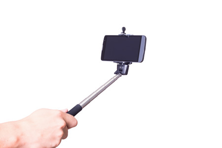 extensible: selfie monopod and cellphone in hand . Isolated on white background .