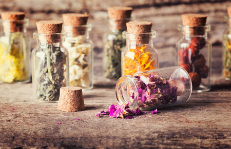 Nature medicine . Herbs in bottles on wooden background .