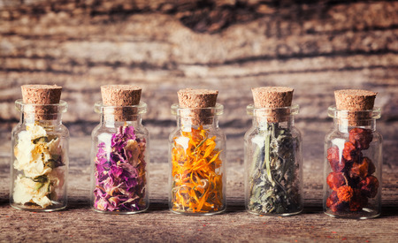 apothecary: Nature medicine . Herbs in bottles on wooden background .