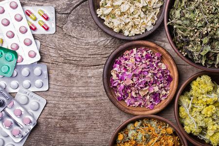 Nature medicine  . Herbs & pills on wooden background .