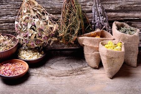 mortero: La medicina natural. Hierbas en el fondo de madera. Foto de archivo