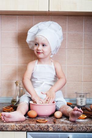 little dough: little girl kneading dough in the kitchen Stock Photo