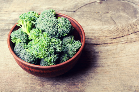 raw food: Fresh broccoli  in bowl on wooden old table close up