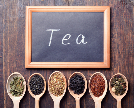 assortment of dry tea on wooden background & blackboard with text Stock Photo