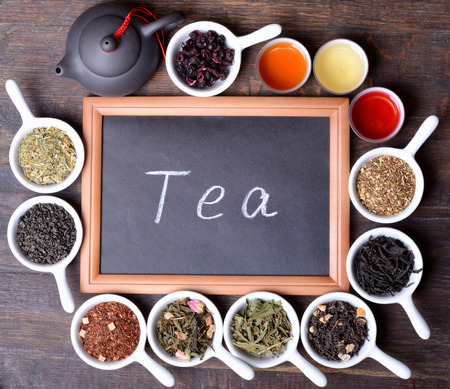teas: assortment of dry tea on wooden background & blackboard with text Stock Photo