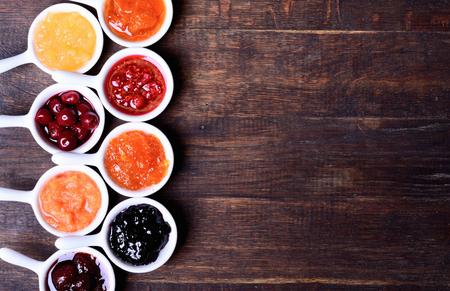 Bowls of tasty jam on wooden background Banque d'images