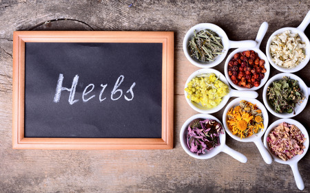 Nature medicine . Herbs & chalk board with text on wooden background . Stock Photo