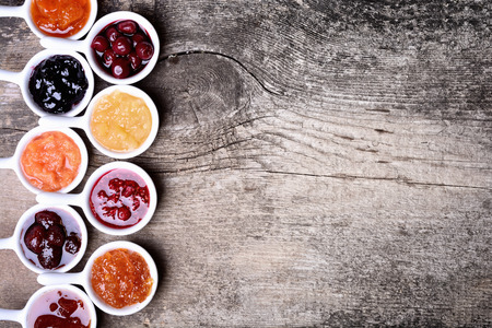 kinds: Bowls of tasty jam on wooden background Stock Photo