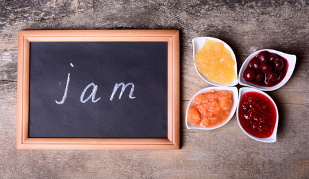 mermelada: Bowls of tasty jam on wooden background & blackboard with text