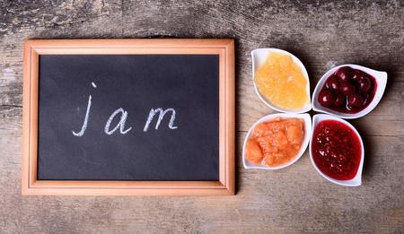 mermelada: Cuencos de deliciosa mermelada en el fondo de madera y pizarra con texto