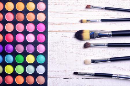 eyemakeup: Make up brush & palette on white wooden background