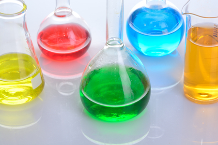 with liquids: Laboratory glassware with colored liquids over reflective table over white