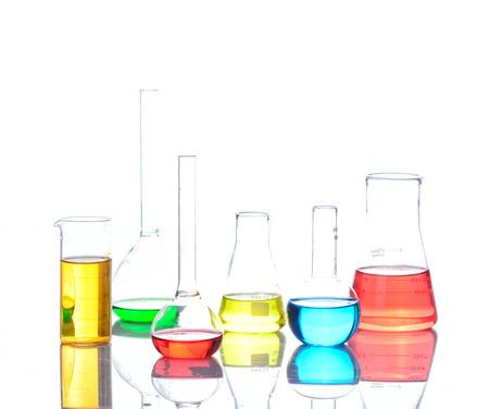 liquids: Laboratory glassware with colored liquids over reflective table over white
